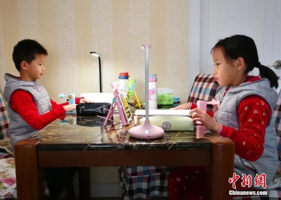 资料图:小学生们正在家中通过电脑、平板电脑等收看直播上课。中新社记者 翟羽佳 摄