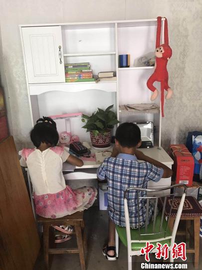 """张小会和妹妹在""""美丽书桌""""前写作业 丁海东 摄"""