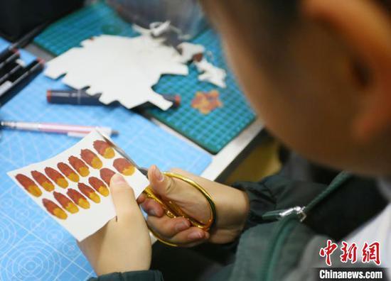 图为小学生将马克笔涂色的纸片进行裁剪。 高展 摄