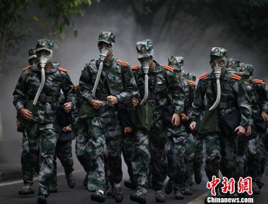 图为拉练活动现场,大学生们戴着防毒面具进行染毒地带穿越。 周毅 摄