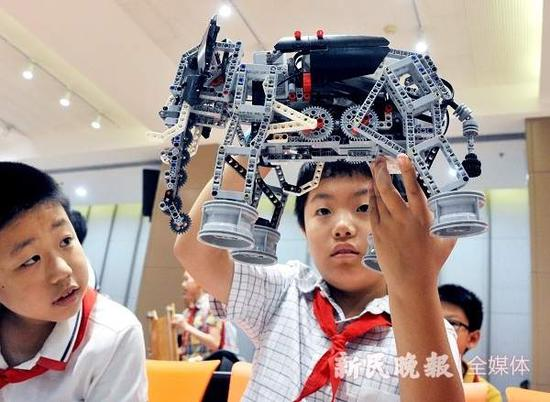 """图说:小学生举起自己创意制作的机器""""猛犸象"""""""