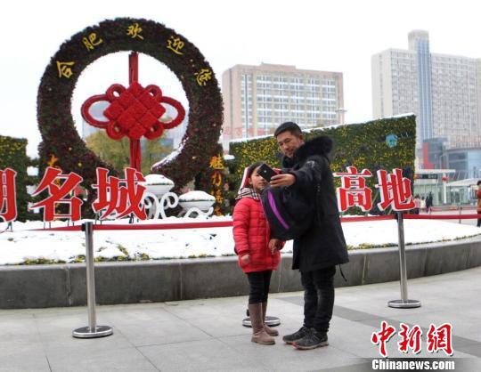 图为父亲与女儿在车站自拍。 夏莹 摄