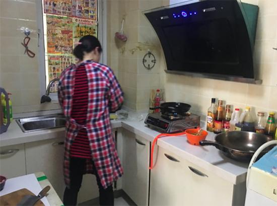 黄晓在出租房里给儿子准备晚饭。