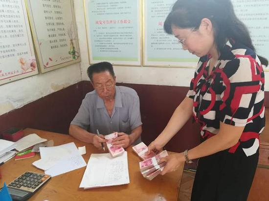 爱心企业工作人员(右)为田京荣一家送去捐款。