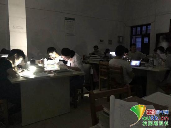 宜春学院学生在用手机照明继续复习。本文图片 中国青年网