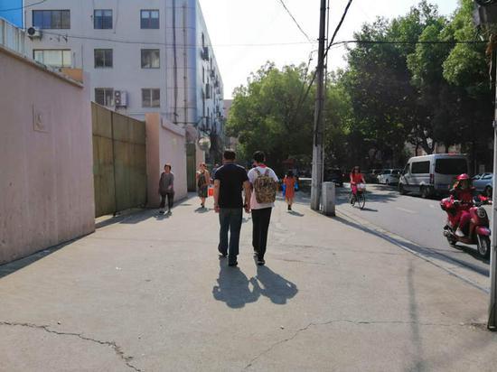 一位爸爸与儿子手挽手走向曲阳二中考点
