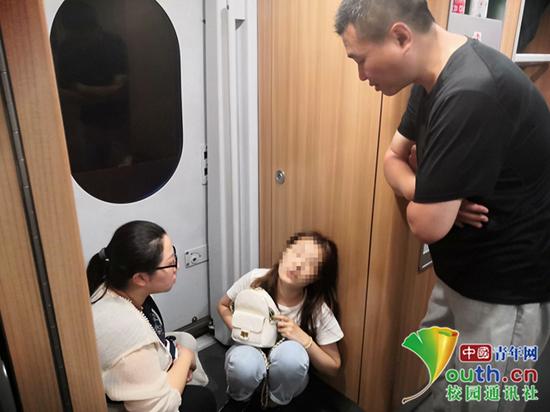 戴奕爽(左一)在列车上与女乘客交流。受访者供图