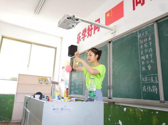 图为志愿者在给小朋友们做水油密度试验 张艳提供