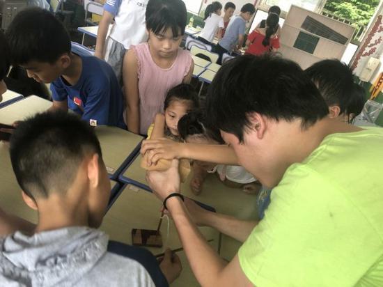 志愿者和小朋友们一起进行钻木取火的实验