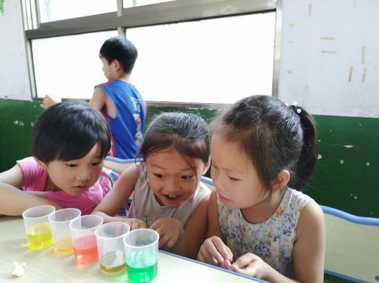 色彩接力实验课上,小朋友们早观察杯子中水颜色的变化,并表现出惊讶的表情。