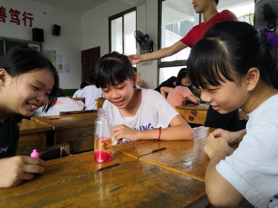 小朋友们在认真观察利用水油密度理论做的火山爆发的实验