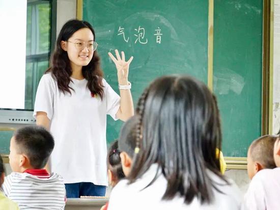 华南理工大学新传心志愿服务队志愿者正在教孩子们播音主持的发声技巧。杨应肖/摄