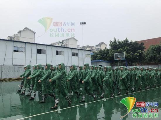 图为新生身着雨衣在练习齐步走。中国青年网通讯员 张珑潆 摄