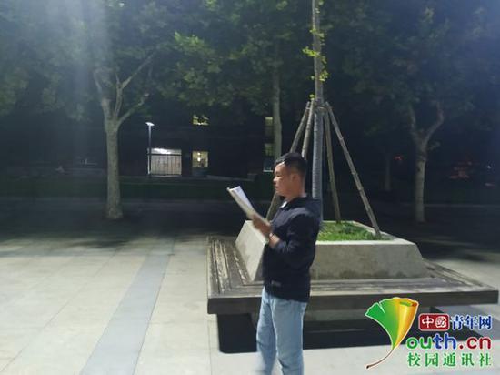 教学楼外的空气好,政法学院的王强从7月21日开始每晚都会在路灯下背书。中国青年网通讯员 闫春旭 摄