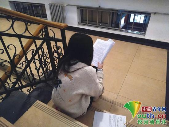 走廊内背书的同学太多,就独自一人静静地坐在楼道内。中国青年网通讯员 闫春旭 摄