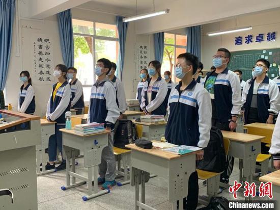 图为高三年级学生起立唱国歌。 武一力 摄