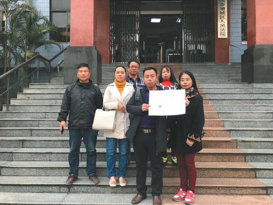 昨日,该案宣判后,几名被拐幼儿的家长拿着判决书在法院门口合影。 受访者供图