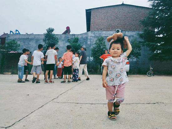 """郑州大学""""转身搬栏锤""""支教小分队的队员们带领着孩子们做游戏。嬉闹声,欢呼声,吸引来了牙牙学语的小朋友。赵燚梦/摄"""
