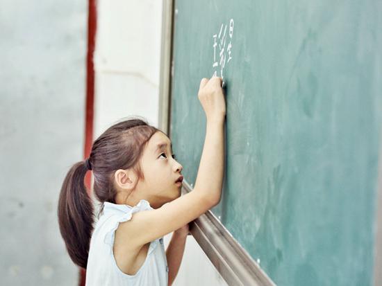 北京航空航天大学红十字会随爱行支教队开课第一天,孩子做着自我介绍,在黑板上写下自己的姓名。尹姜旭/摄