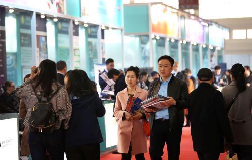 3月24日,一对中国夫妇搜集各大院校的招生简章和宣传材料走过英国院校展区。(图片来源:《欧洲时报》特约记者卞正锋摄)
