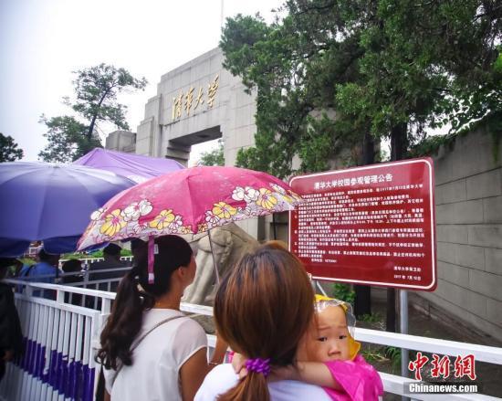 资料图:游客冒雨在清华大学校门外排队等候入校参观。中新社记者 贾天勇 摄