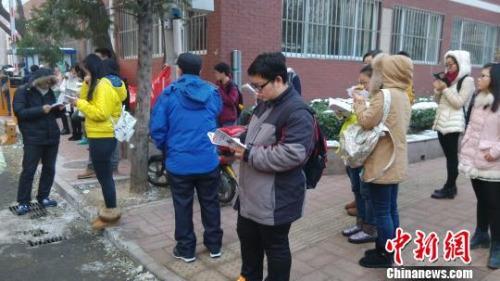 11月29日上午8时,距离2016年国考公共科目笔试开始还有1小时时间,北京市中关村中学双榆树校区的考点外已经聚集了大批等候进场的考生。中新网 张尼 摄