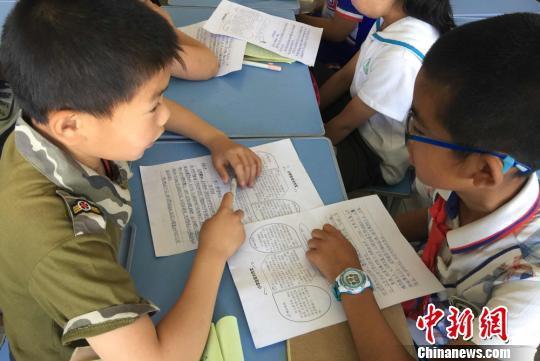 图为四年级学生互相交流讨论作文题目。 刘玉桃 摄