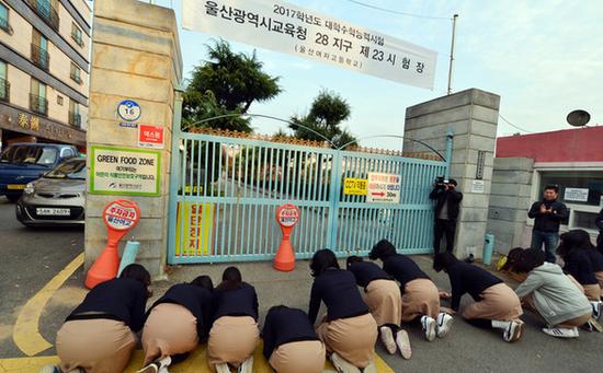 图为考场外学弟学妹们为考生下跪加油。