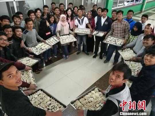 资料图:留学生们入乡随俗,跟着中国老师们一起学包饺子。喻馨锐 摄
