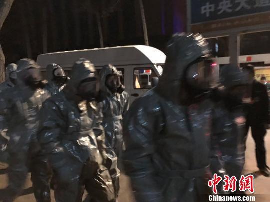十几名身着防护服的人员头戴面具进入事发地。 胡健 摄