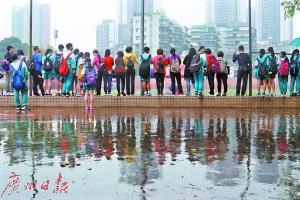 广州市第五中学考场,许多学生冒雨围观中考体育考试。记者骆昌威摄