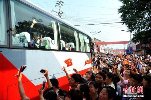 资料图:2016年6月5日上午,19辆大巴车从安徽毛坦厂中学开出,图为家长为参加高考的孩子送行。中新社记者 韩苏原摄