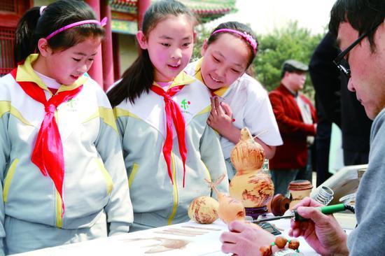 北京市东城区和平里四小的学生在学习葫芦雕刻艺术。 摄/通讯员 梁嘉玮