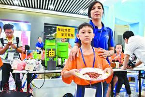 来自中山石岐中心小学的潘志文用自制机器人为妈妈做了一个炒花生米。