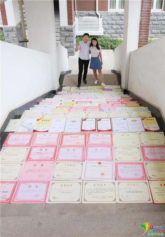 学生情侣将证书摆放在楼梯台阶上拍写真。