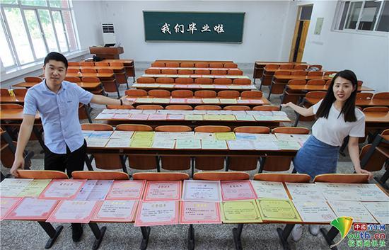 学生情侣将证书摆放在教室里拍写真。