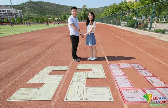 """学生情侣将证书摆放在操场上,摆成""""520""""形状拍写真。"""