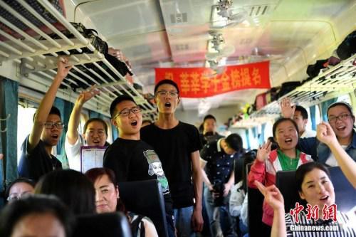 """资料图:2017年6月5日,乘坐""""高考专列""""的学生在车厢内集体加油助威。中新社记者 王舒 摄"""
