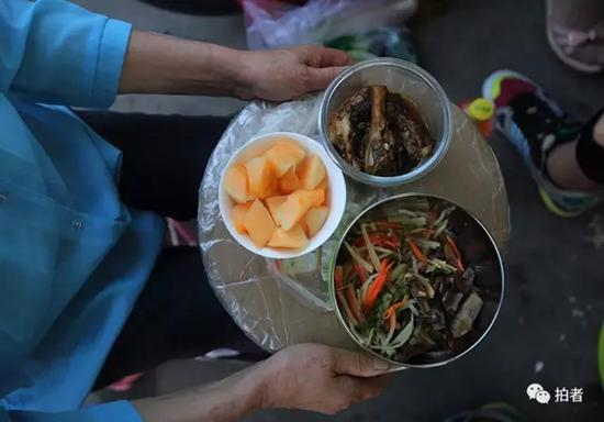 6月2日,毛中东门,65岁的姜奶奶用圆纸板端着两道菜和一盒水果,等着孙子夹菜,每天老人要送两次饭。