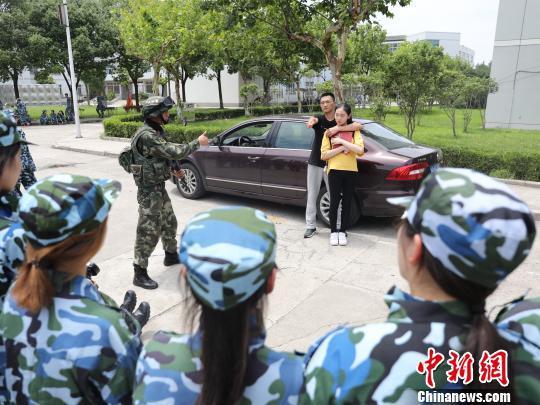 上海高校军训首次新增反劫持演练。图为6日现场武警教官为参训学生演示反劫持要领。 王知洲 摄