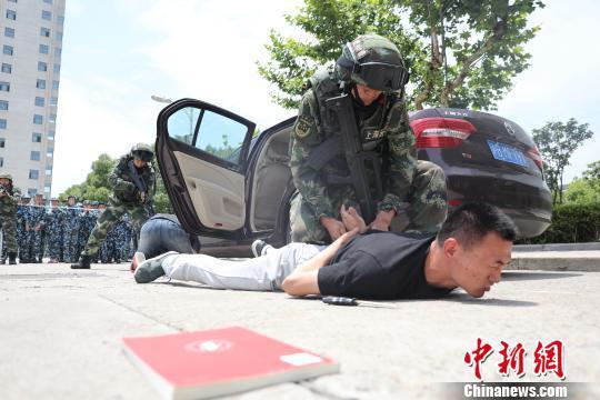 上海高校军训首次新增反劫持演练。图为6日现场武警教官制服歹徒。 王知洲 摄