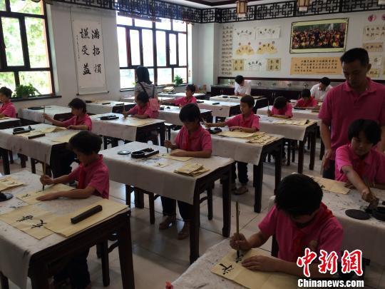 在新疆喀什地区疏附县托克扎克镇中心小学,维族学生们在练习写汉字书法。 蔡敏婕 摄