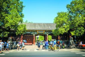 在北京大学东门,来自各地的游客竞相与北大校门合影留念。@视觉中国