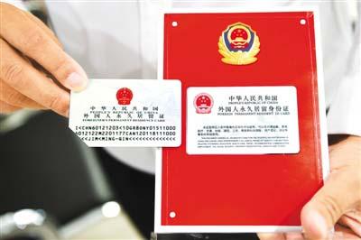 2017年6月16日,2017版外国人永久居留身份证启用。图为在北京市公安局出入境管理局中关村外国人服务大厅,一位外籍人士展示取得的2017版外国人永久居留身份证(右)与旧版的区别。(鞠焕宗 摄)