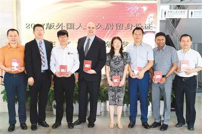 6月16日,在北京市公安局出入境管理局中关村外国人服务大厅,首批获得2017版外国人永久居留身份证的外籍人士合影。(鞠焕宗 摄)