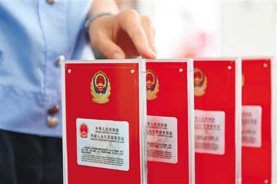 6月16日,在北京市公安局出入境管理局中关村外国人服务大厅,一位工作人员在准备2017版外国人永久居留身份证。(鞠焕宗 摄)
