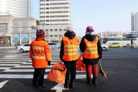 被分派到哈尔滨南岗区城管局保洁一大队的两名研究生(中、右)在巡街保洁时过马路。