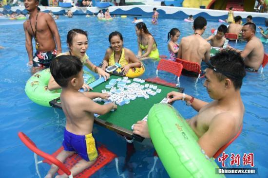 资料图:重庆洋人街一水上乐园举行夏季消暑活动,其中水中玩麻将吸引不少游客参与。陈超 摄