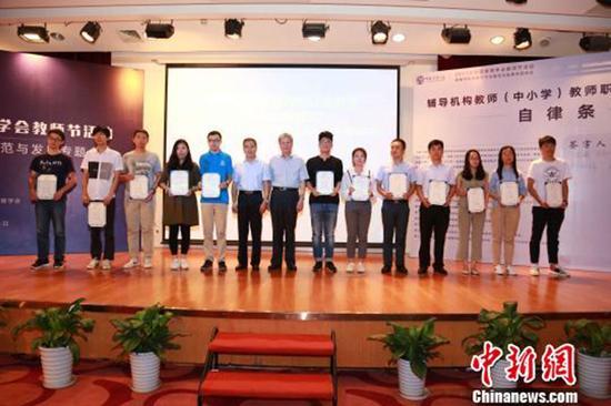 中国教育学会9月11日为首批通过辅导机构教师专业水平等级认证的高级教师颁发证书。 ?#34892;?#32593; 图