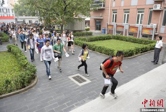 图为考生们进入北京市一处司法考试考点的考场。中新社发 侯宇 摄